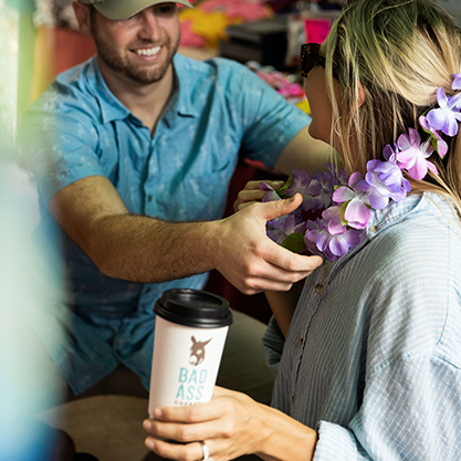 Bad Ass Coffee of Hawaii franchise man places a lei around a woman's neck as she holds her coffee cup