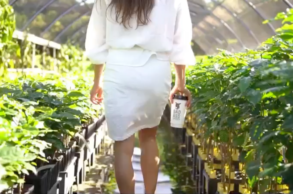 Bad Ass Coffee of Hawaii coffee shop franchise woman walks through greenhouse holding a Bad Ass Coffee cup
