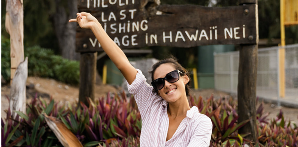 Bad Ass Coffee of Hawaii franchise young woman smiles in front of Hawaii sign
