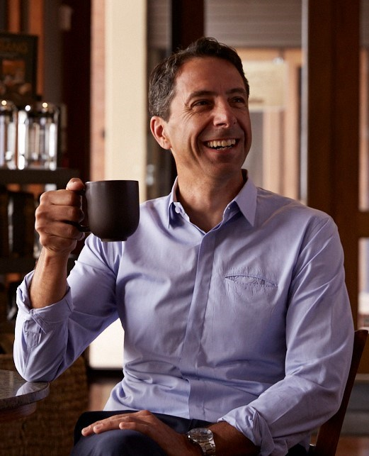 Bad Ass Coffee beverage franchisee new board of director John Coletta smiles with a mug in his hand